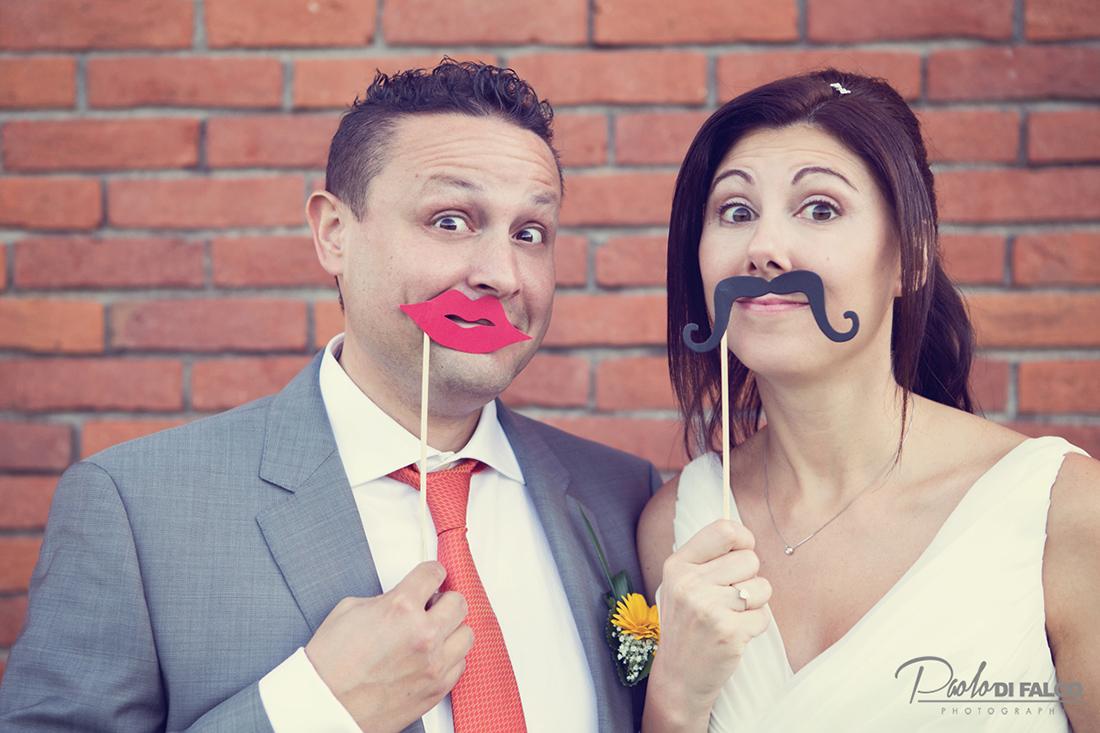 Sposi in posa simpatica con finti baffi e labbra
